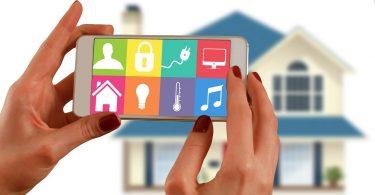 femme tenant une tablette devant une maison