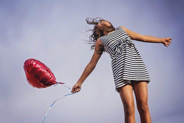 femme en robe rayée avec un ballon rouge en forme de coeur