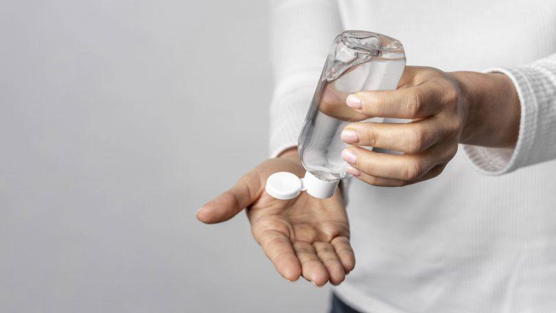 quelques mains mettant sur la main du gel provenant d'un flacon transparent