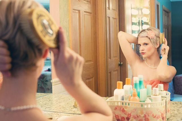 femme se brossant les cheveux devant un miroir