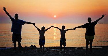 famille les bras levés devant la mer au coucher du soleil