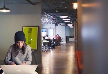 femme travaillant devant un ordinateur dans un bureau ouvert