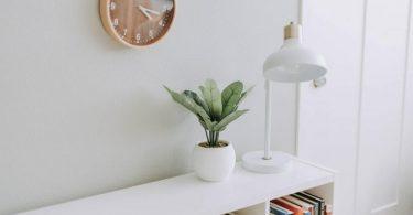 Meuble blanc et horloge en bois sur mur blanc