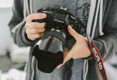 mains tenant un appareil photo