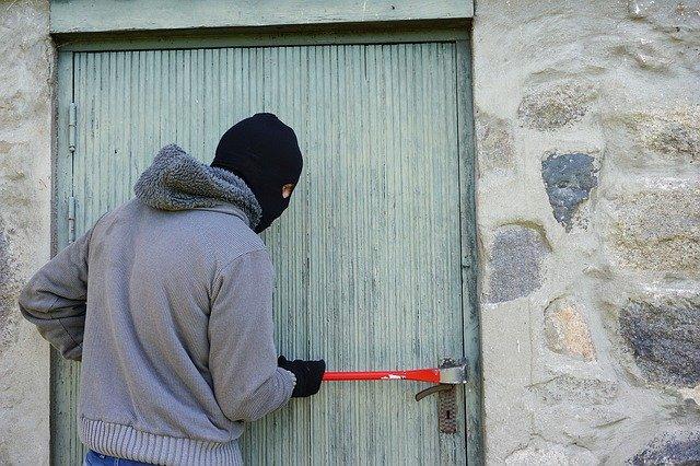 voleur faisant une effraction de porte