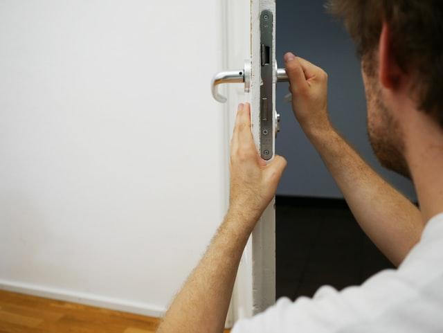 homme touchant une serrure de porte | locataire assurance habitation