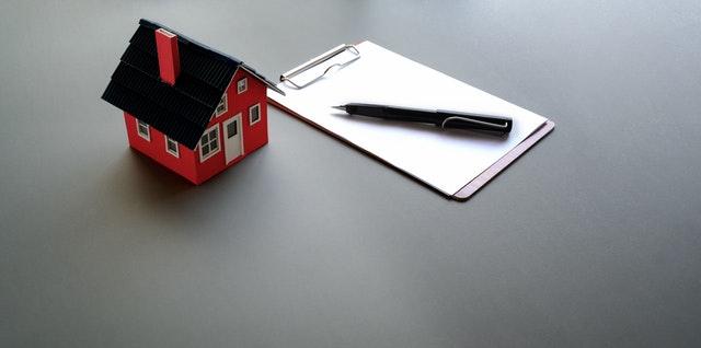 petite maison sur table avec papier et crayon