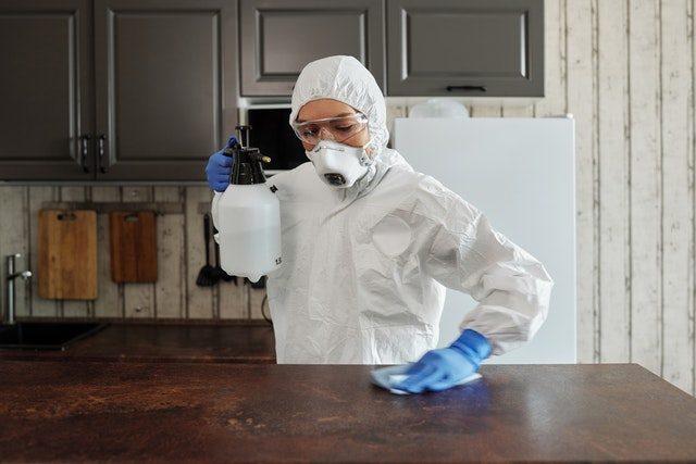 Personne en combinaison nettoyant la cuisine