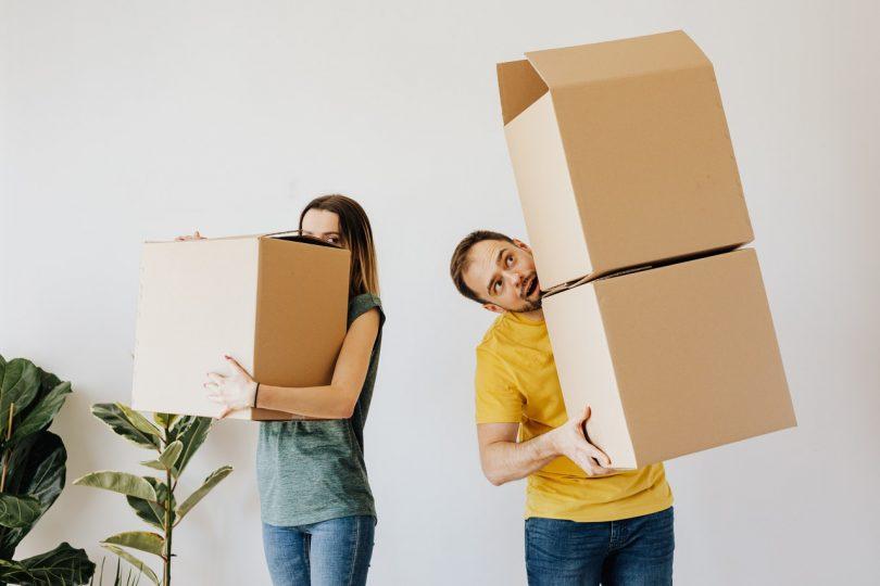 couple portant des cartons de déménagement