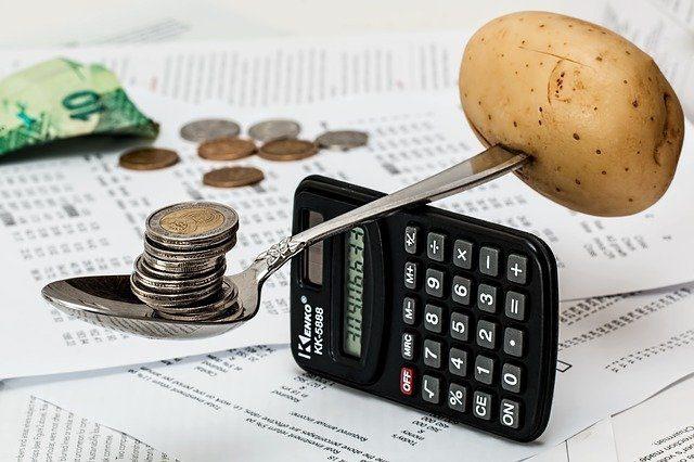 une calculatrice de l'argent et une pomme de terre en équilibre