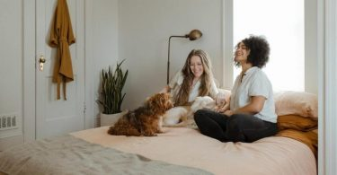 deux femmes assises dans une chambre avec un chien