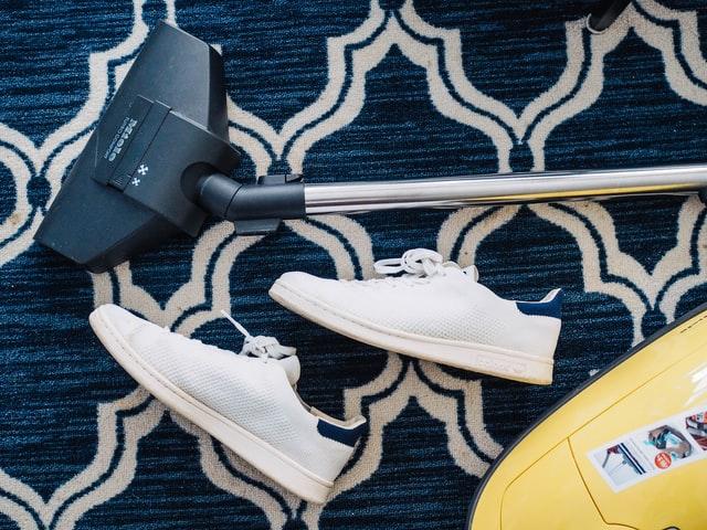 aspirateur et chaussures sur un tapis