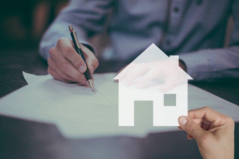 signature de document devant une main tenant une maison
