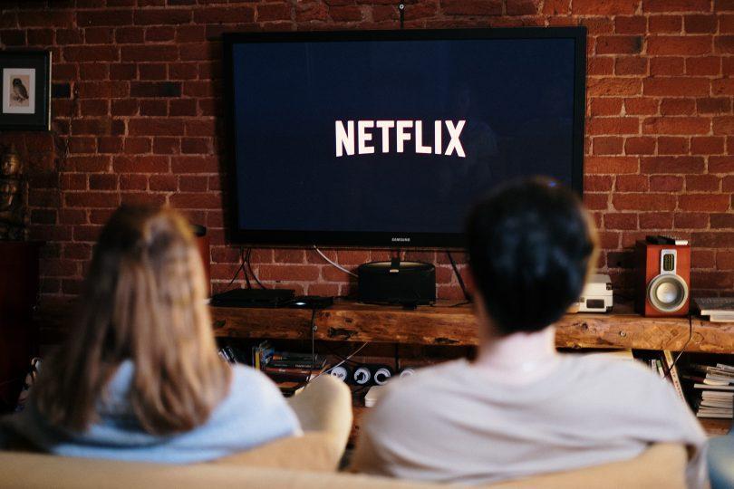 Couple assis dans un canapé regardant la tv