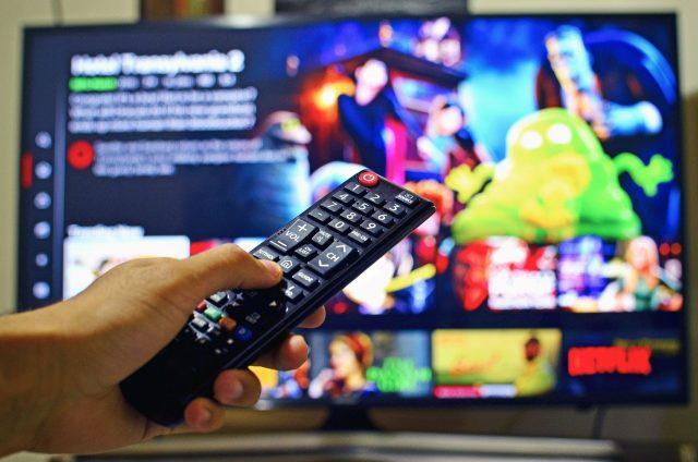 main tenant une télécommande de télé