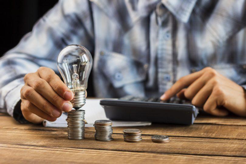 main tenant une ampoule sur des pièces de monnaie