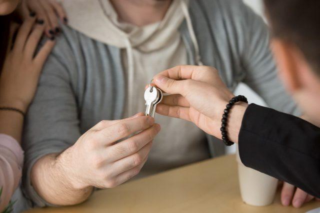 main donnant des clés à un couple