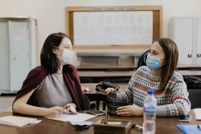 deux filles portant le masque dans une salle de classe