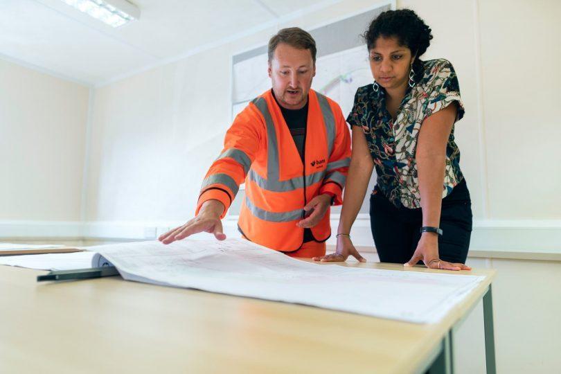 un homme et une femme devant des plans de construction