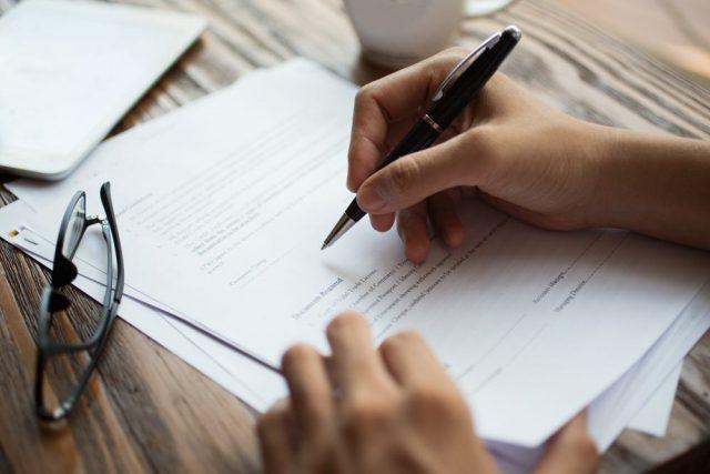 Main signant un papier